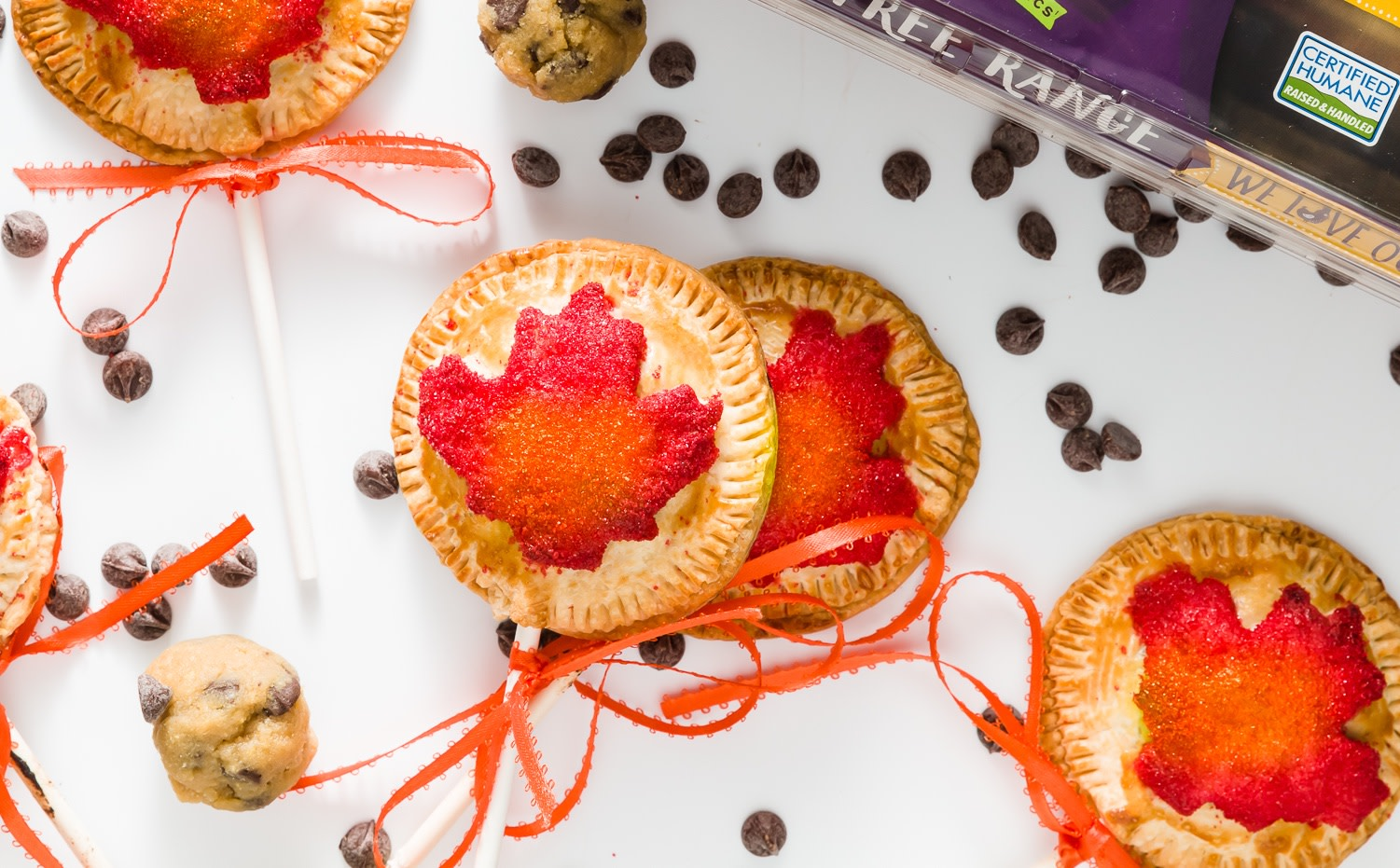 Fun and festive pie pops made with flaky pie crust stuffed with chewy chocolate chip cookie dough. Each pie pop is decorated with a red pie crust leaf. | nelliesfreerange.com