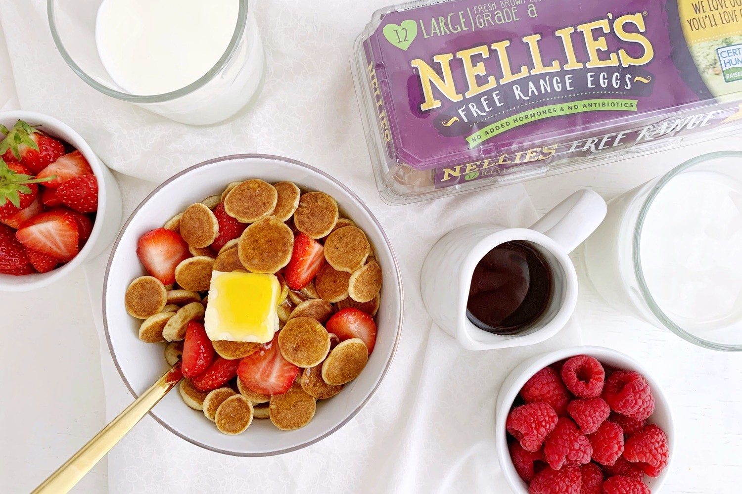Mini buttermilk pancakes topped with a pat of butter, maple syrup. and served in a bowl with a spoon. | nelliesfreerange.com