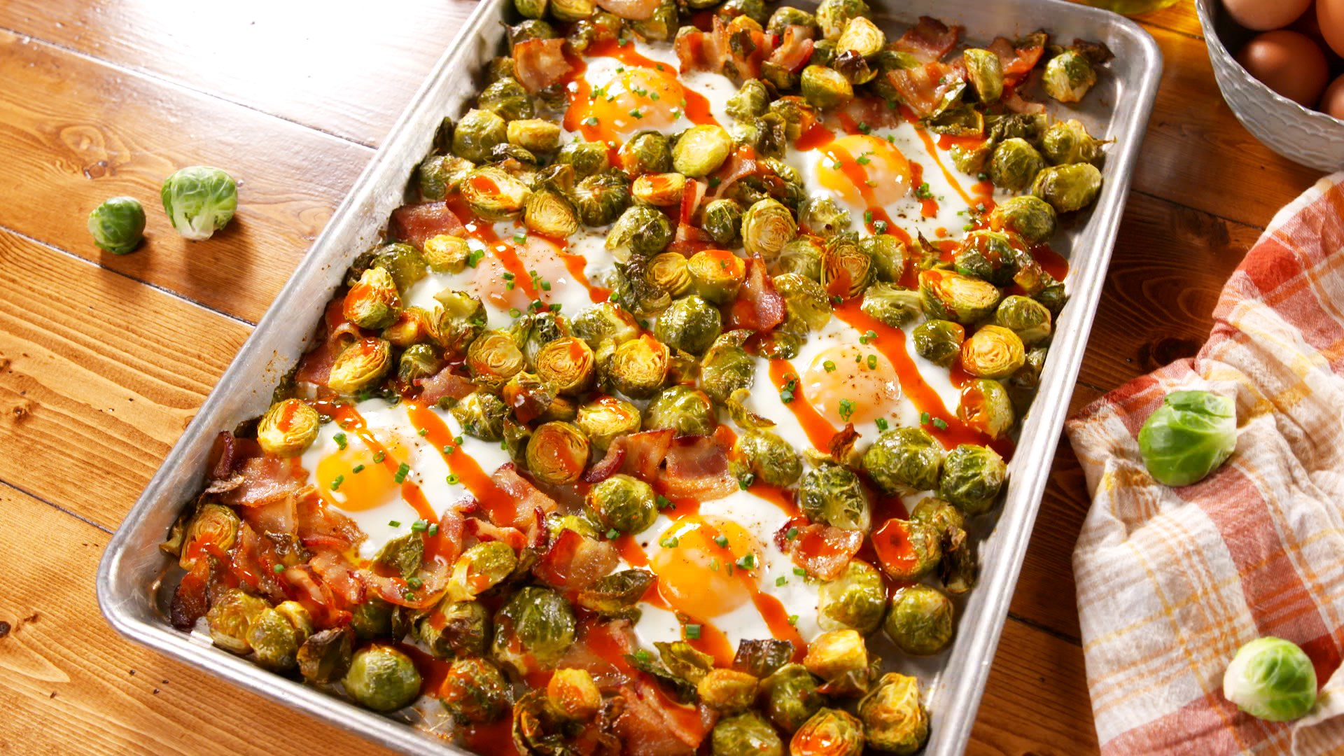 Quick and easy sheet pan hash recipe featuring crispy Brussels sprouts, bacon, buffalo sauce and baked eggs. | nelliesfreerange.com