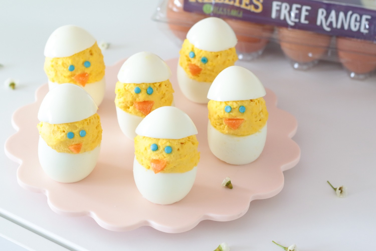 Cute, simple, kid-friendly deviled egg chicks assembled vertically with carrot noses and blue sprinkle eyes. | nelliesfreerange.com