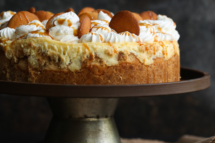 Classic banana pudding made into a sweet and tangy cheesecake topped with bananas, wafers, and whipped cream. | nelliesfreerange.com