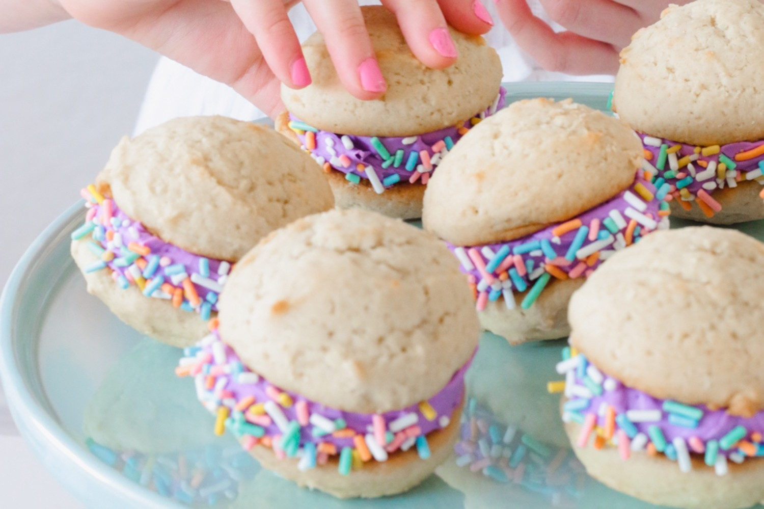 Colorful vanilla whoopie pies featuring two soft cookies filled with fluffy buttercream and rolled in sprinkles. | nelliesfreerange.com