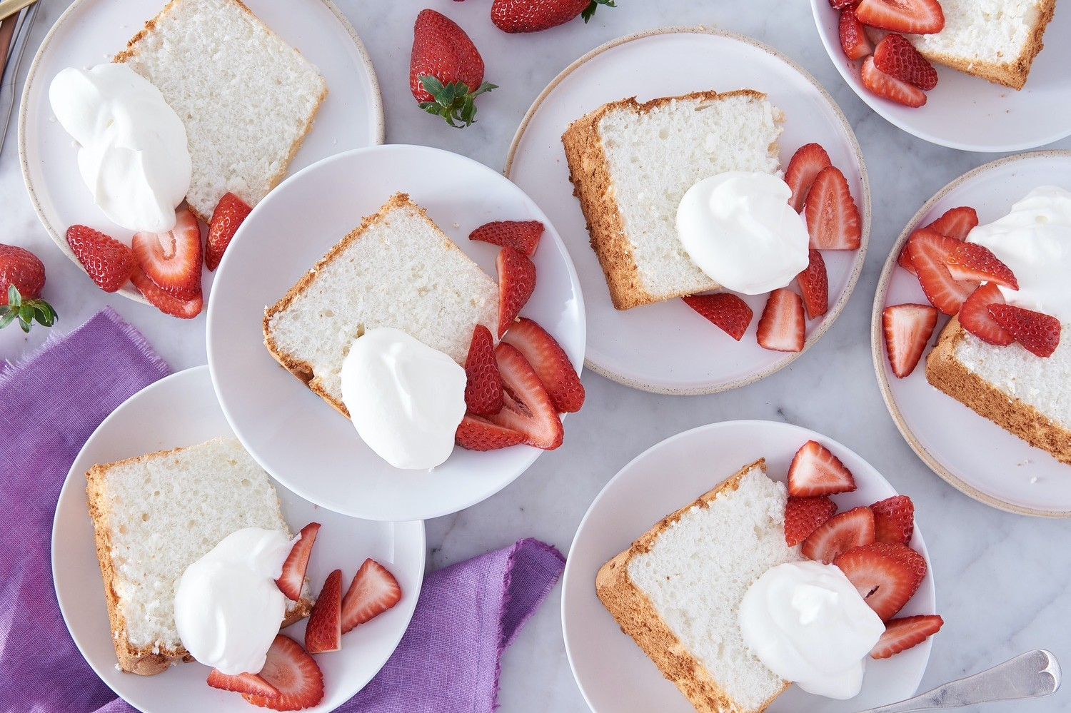 Light and pillowy angel food cake topped with whipped cream and fresh berries. | nelliesfreerange.com