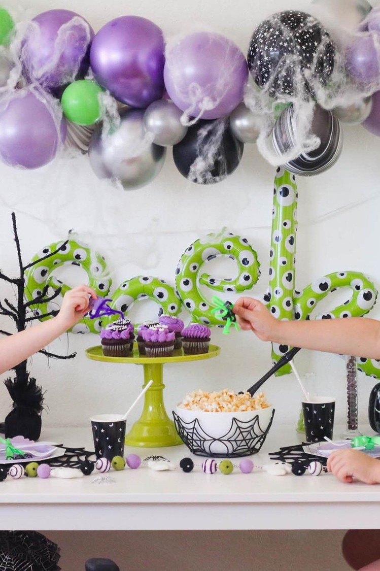 Halloween themed party, with purple people eater cupcakes, DIY upcycled egg carton spiders, and spooky balloons covered in spider webs.
