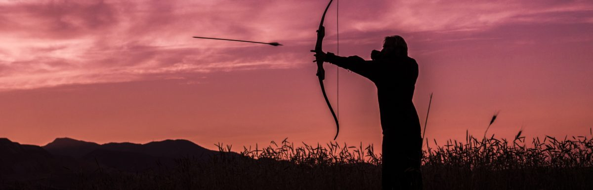 A man shooting a bow and arrow at sunset
