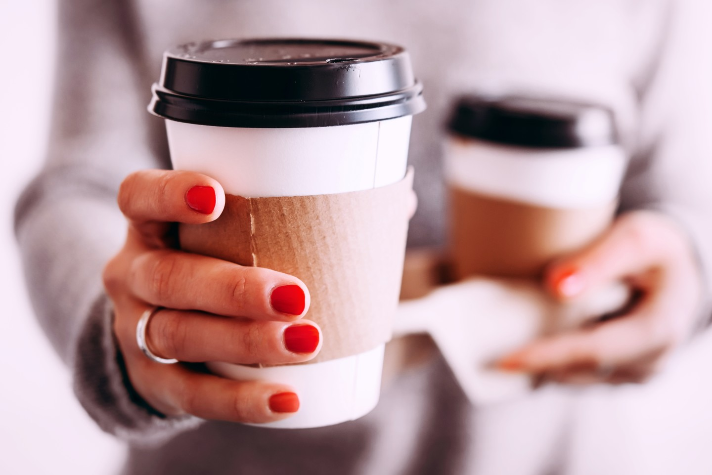 woman-hold-out-coffee-cup