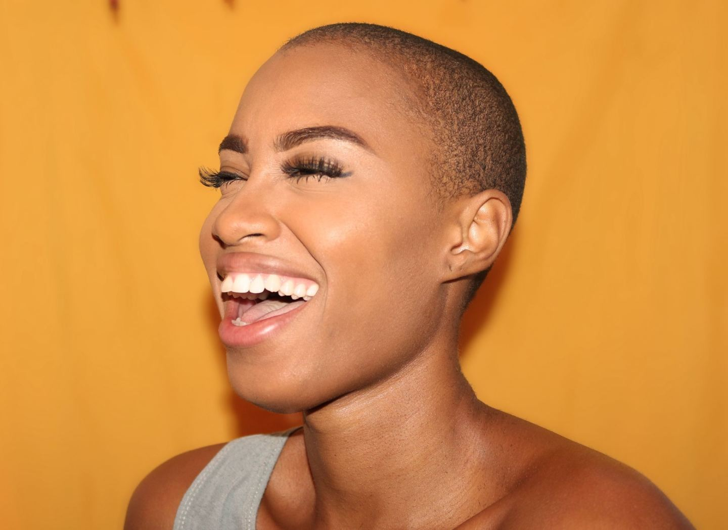 woman shaved head long eyelashes yellow background smile