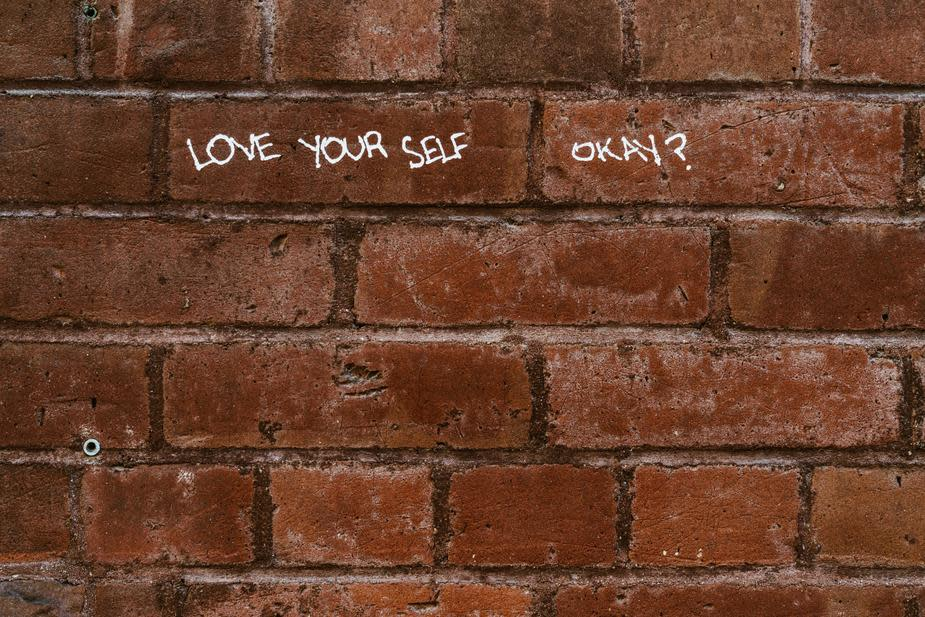 love yourself brick wall writing