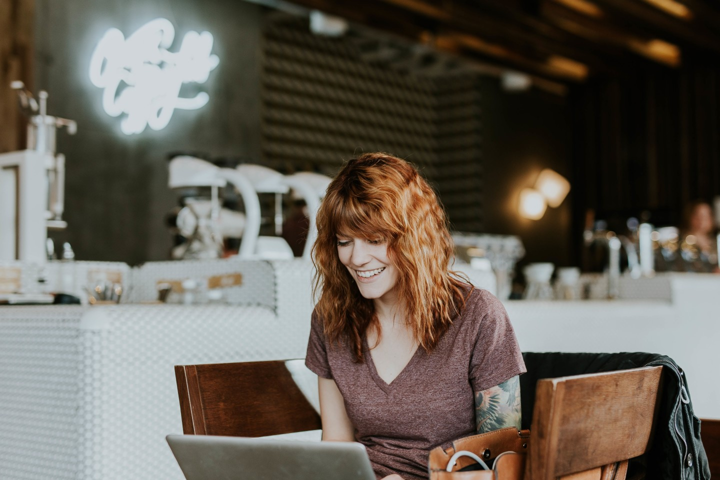 redhead on laptop in coffee shop