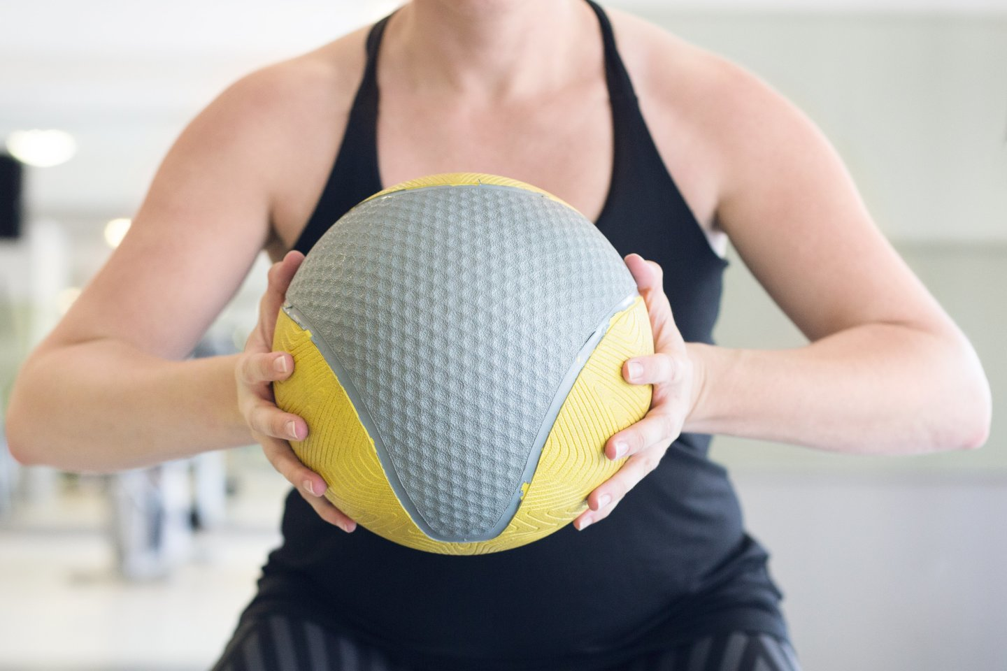 woman squeezing medicine ball
