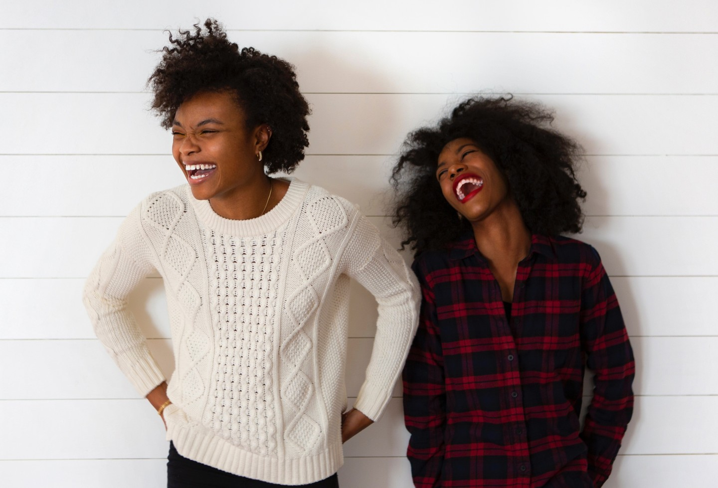 women-laughing-against-white-wall