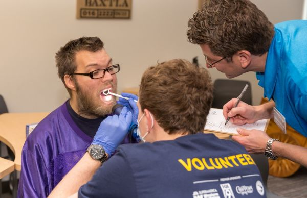 Volunteers examining patients mouth