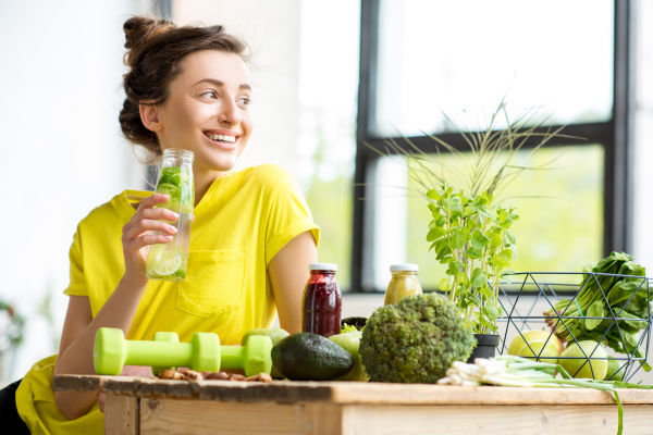 Girl sitting at table after exercising surrounded health food options