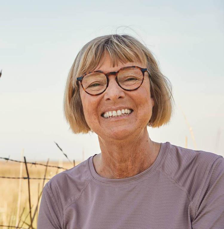 En äldre person med glasögon ler brett. Foto.