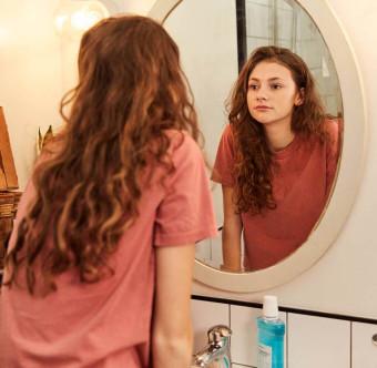 En person ser sig i spegeln i badrummet. Foto.