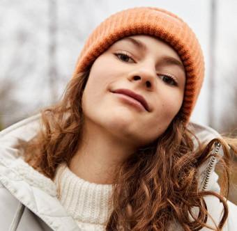 Ung kvinna med vinterkläder ler mot kameran. Foto.
