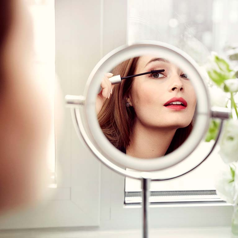 Kvinna målar ögonfransar med mascara