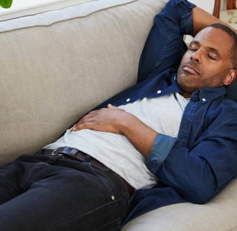 En man vilar på en soffa med handen över magen. Foto.