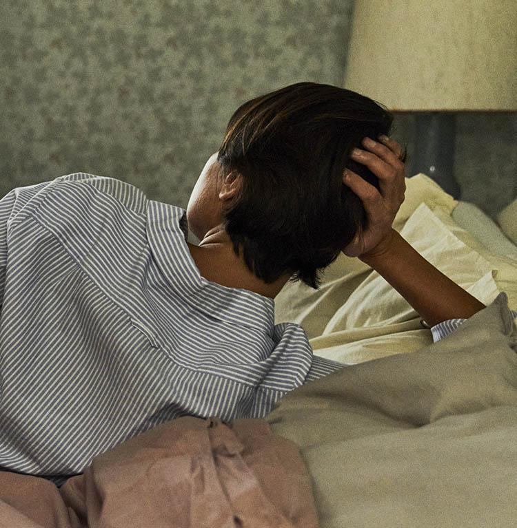 En person ligger bortvänd i en säng och stöder huvudet i handen. Foto.
