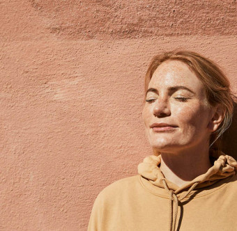 En person står vid en vägg och njuter av solen. Foto.