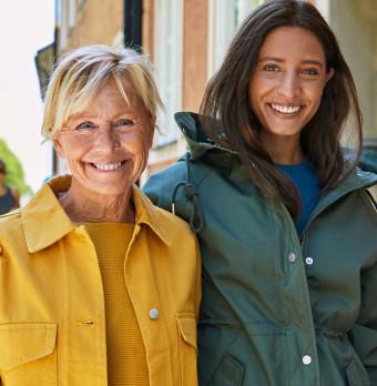 Två leende kvinnor i olika åldrar. Foto.