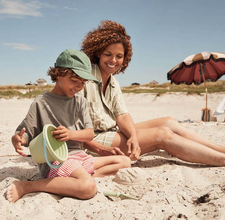 En vuxen och ett barn sitter på sandstranden. Foto.