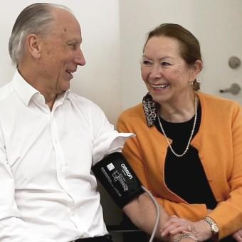 Äldre dam och man mäter blodtrycket