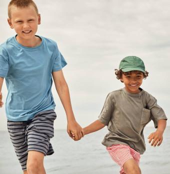 Två barn springer medan de håller händerna. Foto.