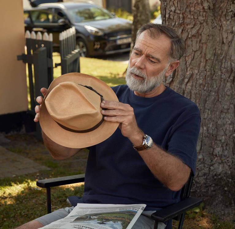 En äldre man sitter under ett träd och håller en solhatt. Foto.