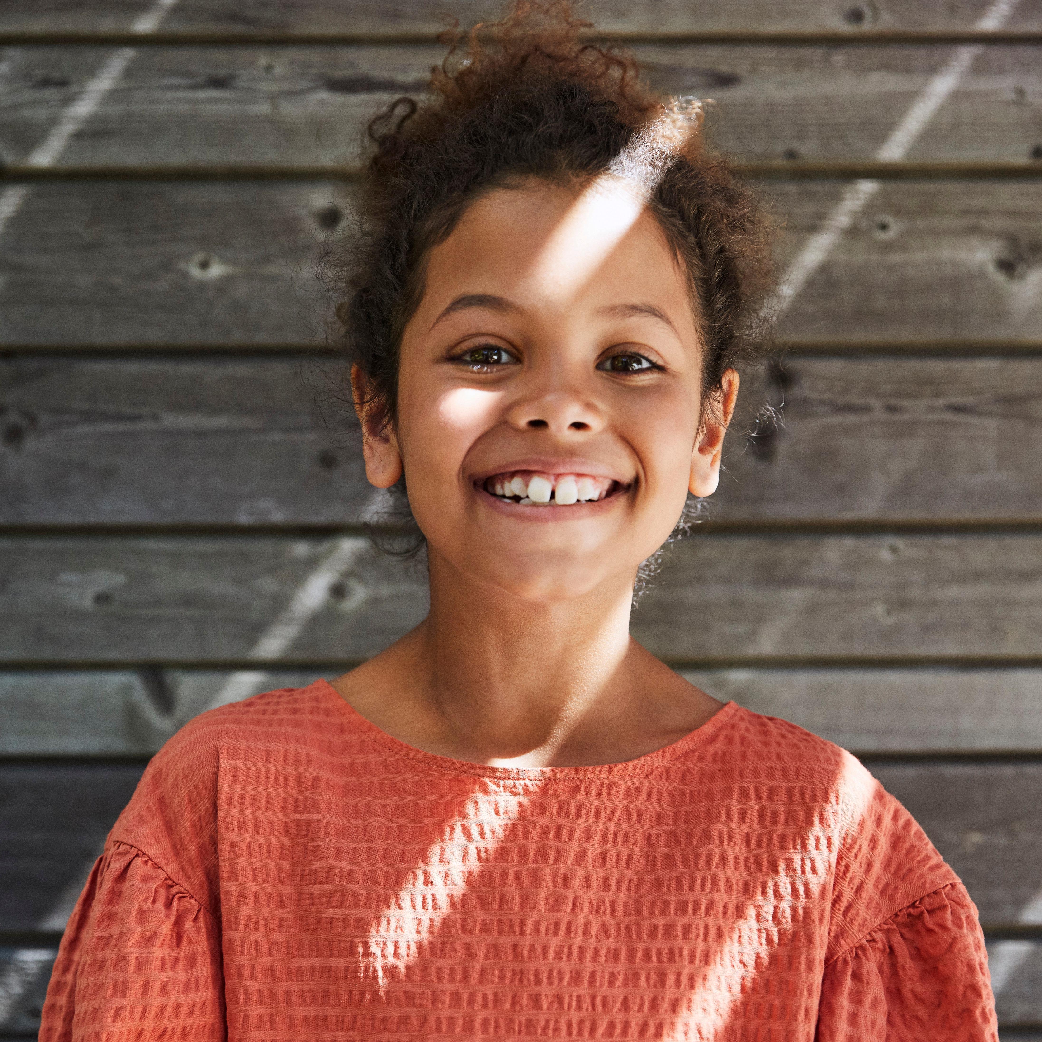 Ett barn står upprätt framför en trävägg. Foto.