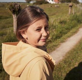 En flicka står vid ett gräsfält. Foto.