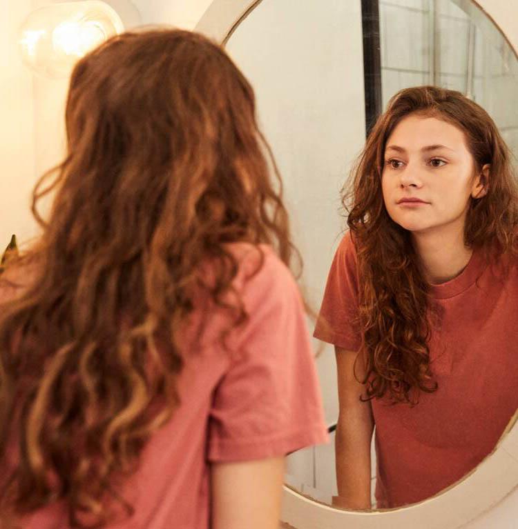 En ung kvinna ser sig i spegeln. Foto.