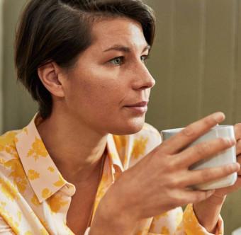 En person ser fundersam ut och håller en kopp varm dryck. Foto.