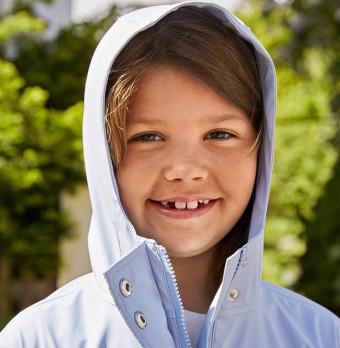 Ett barn som har tappat sina första mjölktänder ler. Foto.