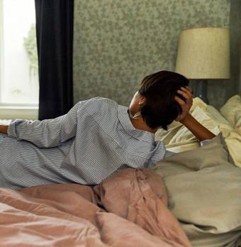 En person ligger i sin säng. Foto.