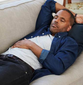 En man vilar på soffan. Foto.