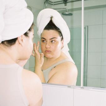 Kvinna i spegel som använder Mantle-produkter. Foto.