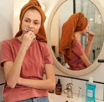 En person står i ett badrum och borstar tänderna. Foto.
