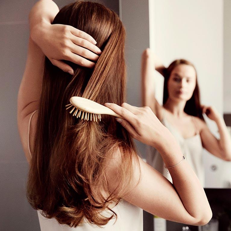 Kvinna som borstar håret