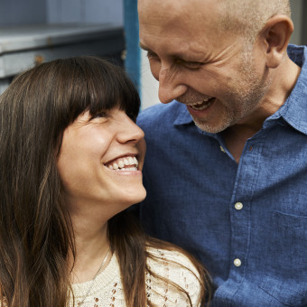 Ett glatt par ler åt varandra. Foto.