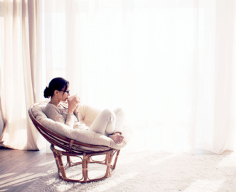 Kvinna sitter i fåtölj med kopp