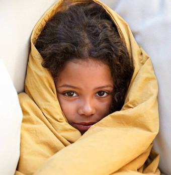 En flicka är insvept i en filt. Foto.