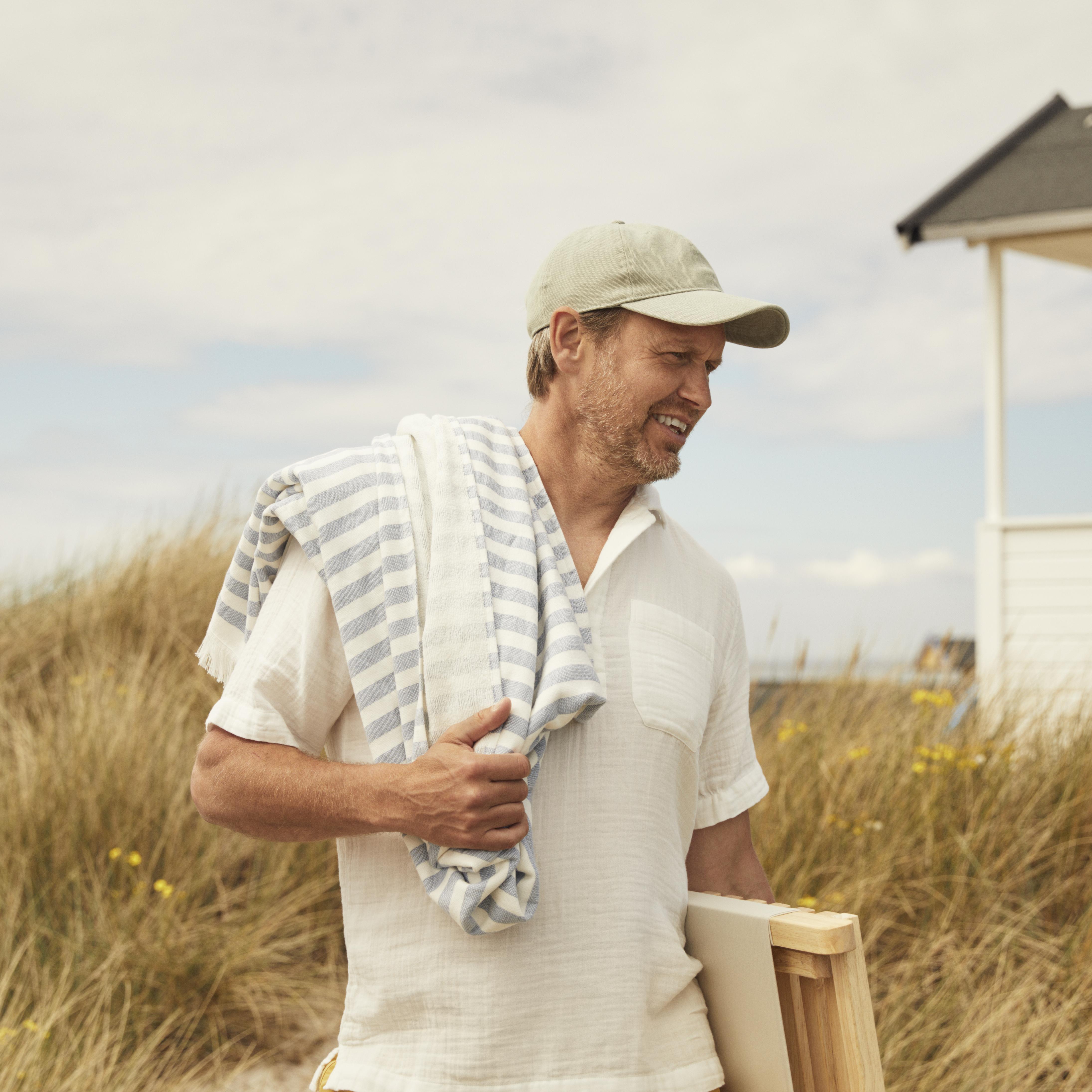 Man på strand i keps. Foto.