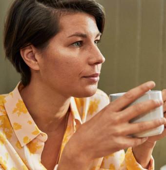 En person dricker kaffe och ser fundersam ut. Foto.