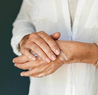 En person smörjer in sina händer. Foto.