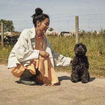Kvinna ute i solen med en hund. Foto.