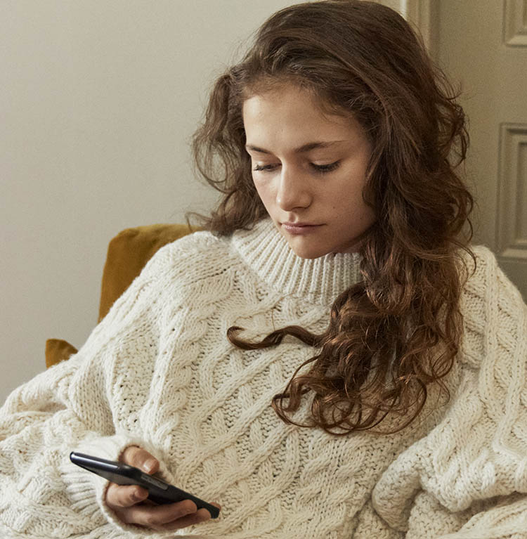 En person med stickad tröja sitter i en soffa och ser på sin mobil. Foto.