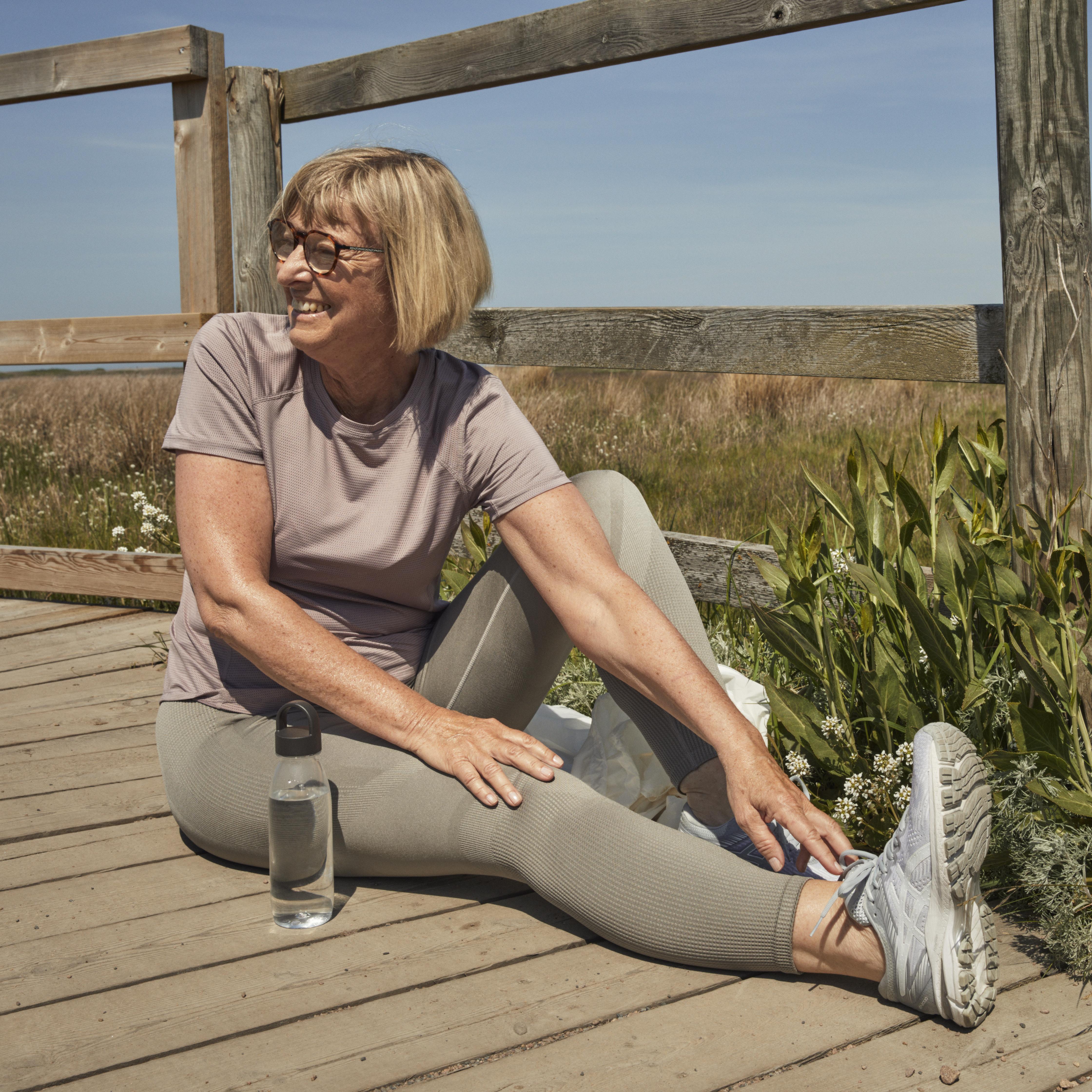 Senior kvinna i träningskläder i solen. Foto.
