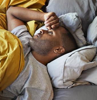 En man ligger vaken i sängen. Foto.