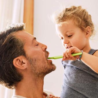 Barn och vuxen borstar tänder